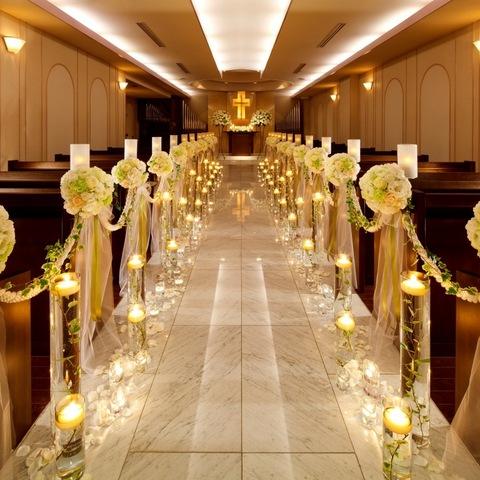 チャペル 扉の奥に広がる荘厳なチャペル。白亜の壁とウッドベンチの中央に優しく輝く十字架が浮かび上がります。