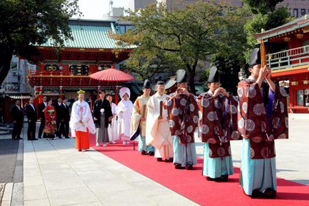 【参進】楽人が天空に奏でる雅楽の音色を先頭に、神職・巫女・新郎新婦・ご媒酌人・ご両親・ご親族の順番で、赤い絨毯(じゅうたん)が敷かれた社殿までの約60mを歩きます。新郎新婦には巫女が朱傘を添えています。雨天時は、雨天用通路から参進いたします。